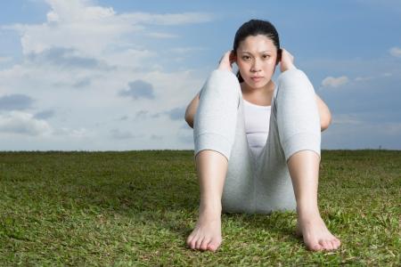 Beautiful active Asian woman doing sit ups on grass. Stock Photo