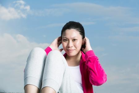 sit up: Beautiful active Asian woman doing sit ups on grass. Stock Photo