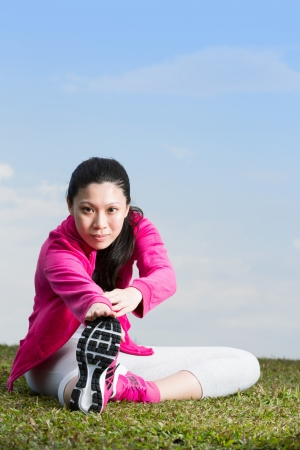 Asian female runner stretching before going running. photo