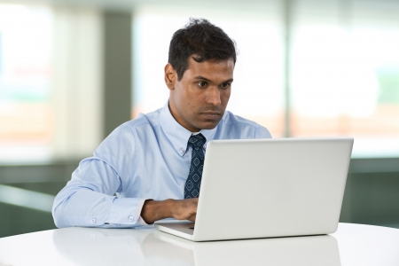 indian professional: Indian Business man working on his laptop. Stock Photo