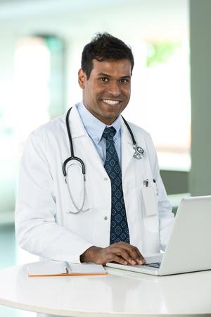 Office uniforms: M�dico indio macho lleva una bata blanca, sentado en un escritorio de trabajo con su computadora port�til.