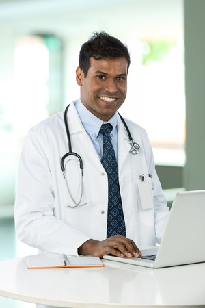 Male Indian doctor wearing a white coat, sitting at a desk working with his laptop.  photo