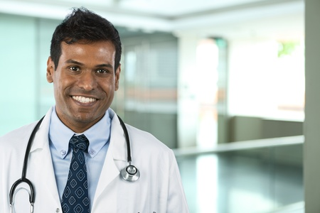 Male Indian doctor wearing a white coat and stethoscope. photo