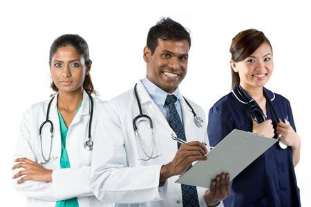 cultural and ethnic clothing: Portrait of happy young Indian doctor holding clip[ board with his team in background. Stock Photo