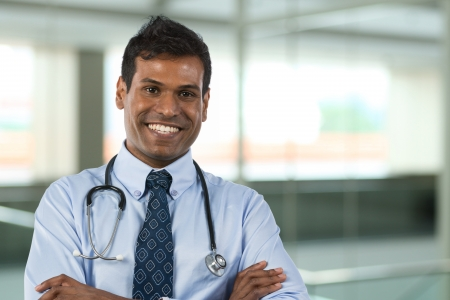 general practitioner: Male Indian General Practitioner or GP standing in hospital with background out of focus.  Stock Photo