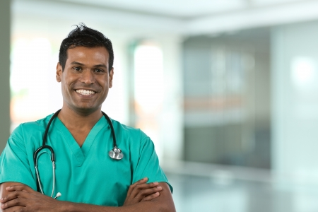 Male Asian doctor holding a digital tablet & wearing a lab coat plus stethoscope. Stock Photo