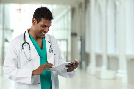 Male Asian doctor holding a digital tablet & standing in a hospital.
