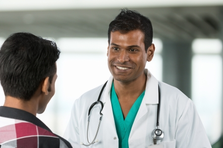 Male Indian Doctor talking to a patient in a hospital.  photo