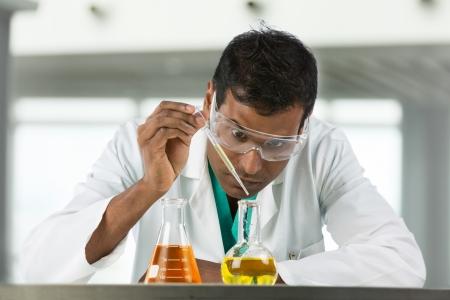laboratorio clinico: Indian investigador cient�fico macho palabras en un frasco de l�quido en un laboratorio.