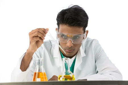 indian male: Indian male scientific researcher looking at a flask of liquid. Isolated on white background.