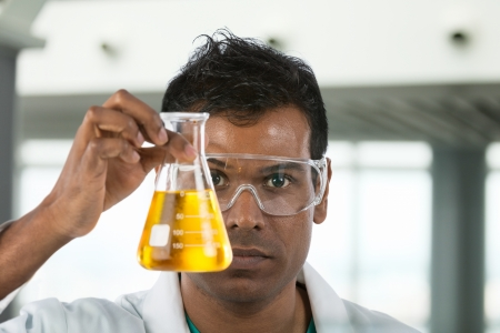 beaker: Científico indio mirando vaso de precipitados de líquido en un laboratorio.