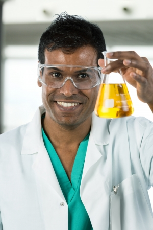 Portrait version of an Indian scientist looking at beaker of liquid in a lab. photo