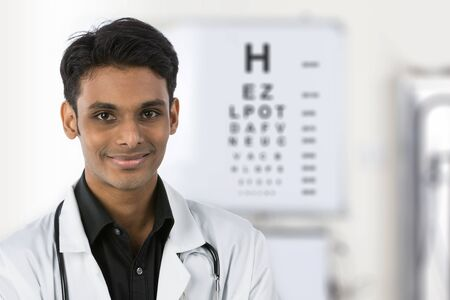 Indian doctor with an eye test chart out of focus in the background. photo