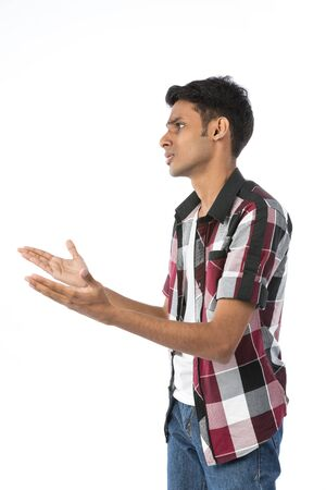Side view of a frustrated young Indian man. Isolated against white background. photo