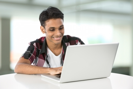telecommuting: Happy Asian man working on his laptop. Stock Photo