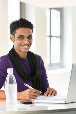 hombre sentado: Feliz hombre asi�tico que trabaja en su computadora port�til. Foto de archivo