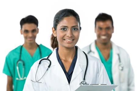 asian medical: Indian doctor wearing a white coat with stethoscope. Her team are out of focus in background.