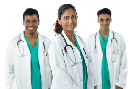 Indian doctor wearing a white coat with stethoscope. Her team are out of focus in background. photo