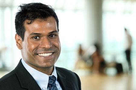 east indians: Happy Indian business man at the office. Stock Photo
