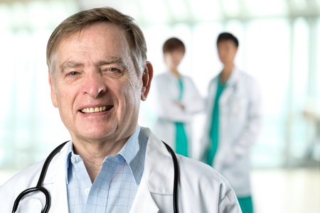 Senior Male doctor with colleague in the background out of focus. photo