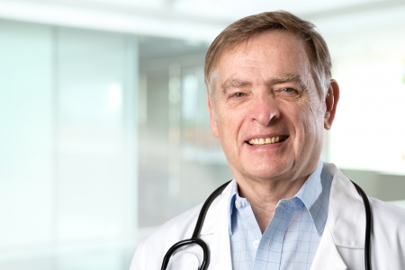 Mature caucasian doctor wearing a white lab coast and stethoscope. photo