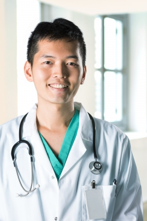 Asian doctor standing in corridor of a hospital wearing white coat with stethoscope.  photo