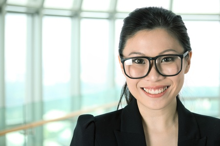 Portrait of a happy Asian business woman in a modern office building. photo