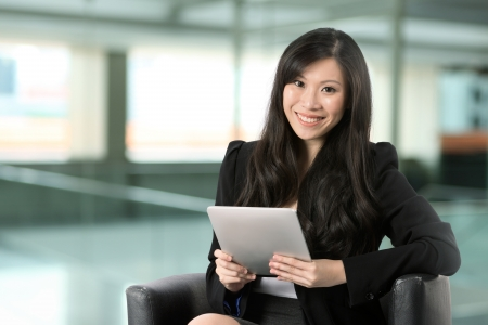 executive chair: Asian Business woman using Digital Tablet at work.  Stock Photo