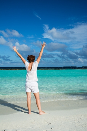 Happy woman standing with her arms out stretched on a tropical beach
