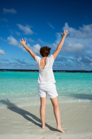stretched out: Happy woman standing with her arms out stretched on a tropical beach  Composed in the middle of the image  Stock Photo