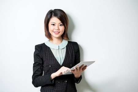 Beautiful Asian business woman using tablet computer. Leaning against a white wall. photo