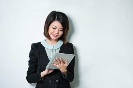 Beautiful Asian business woman reading tablet computer. photo