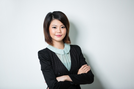 chinese wall: Happy Chinese business woman leaning against a wall. Stock Photo