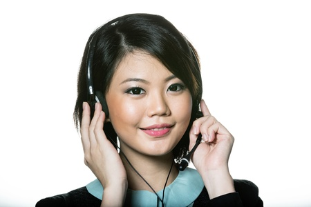 Happy Asian woman wearing a call center headset. Isolated on white background. photo