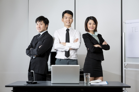 authoritative: Three Asian Business colleagues standing in an office.