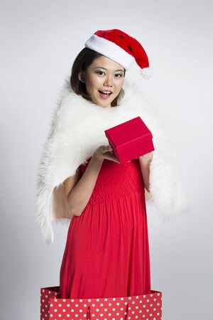 Happy Chinese girl jumping out of a bag wearing a santa hat photo