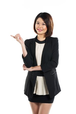 indicating: Happy Chinese business woman pointing her finger towards empty space