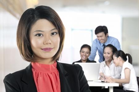 actitud positiva: Hermosa mujer de negocios chino con colegas que trabajan detr�s.