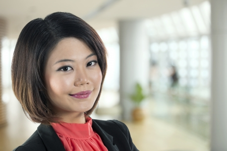 business woman standing: Portrait of a happy Chinese business woman.