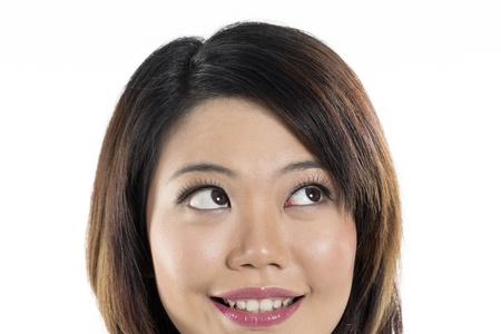 Closeup of a cute Chinese woman looking up into the corner. Isolated on white background. photo