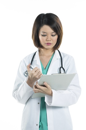 Portrait of a pretty Female Chinese doctor wearing a green scrubs and lab coat writing on a clipboard. Isolated on white. photo