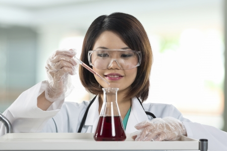 Chinese woman scientist or Doctor looking at a liquid solution. photo