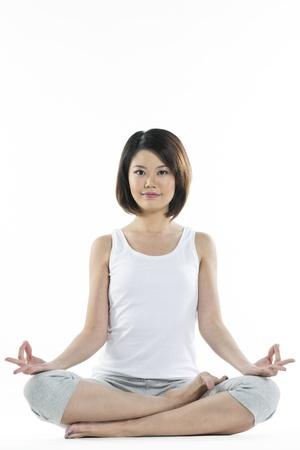 mujer china: Retrato de una bella mujer china en posici�n de yoga del loto.