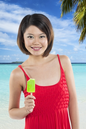 Chinese woman eating a green lime ice lolly. photo