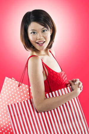 Beautiful & happy Chinese woman holding shopping bags.  Stock Photo - 16728979