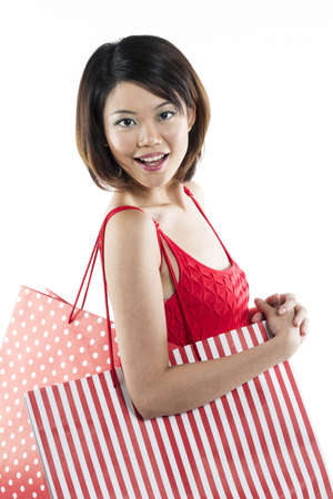 Beautiful & happy Chinese woman holding shopping bags.  photo