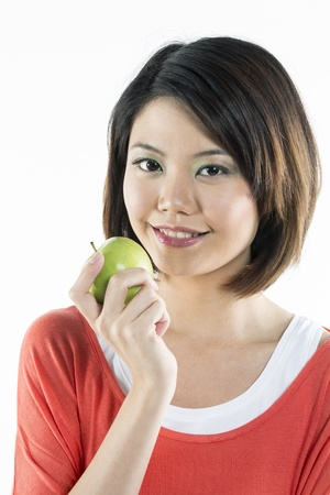 Portrait of a beautiful Chinese woman holding an apple. Healthy eating concept. photo