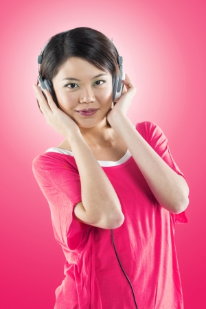 Trendy Chinese woman listening to music on headphones in front of a pink wall. Stock Photo - 16728884
