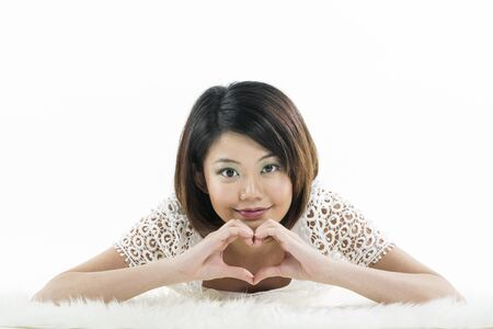 Sweet Chinese lady making a heart shape sign with her hands. photo