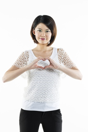Cute Chinese lady making a heart shape sign with her hands. photo
